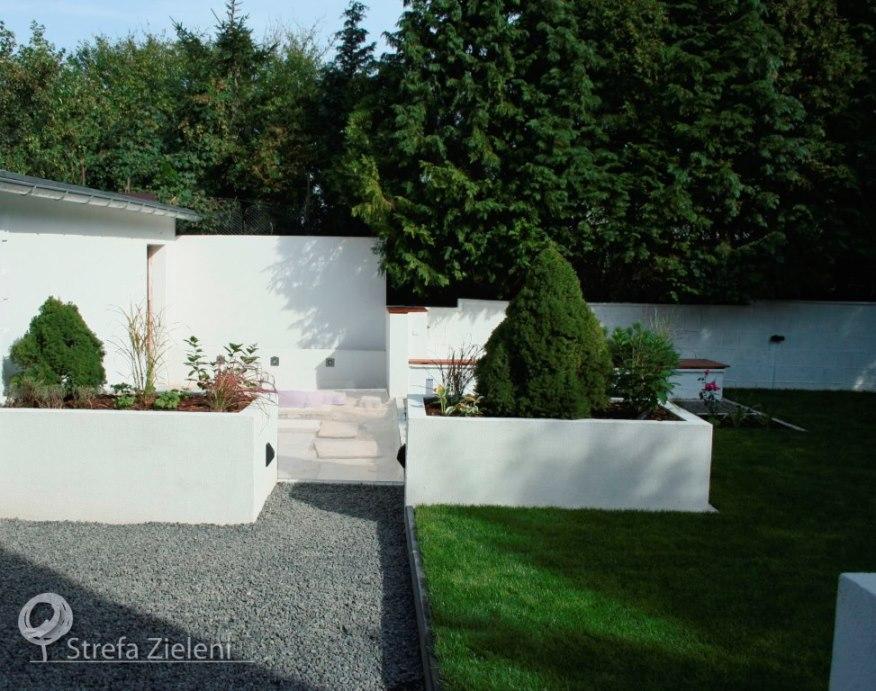 Ogród z białymi murowanymi donicami