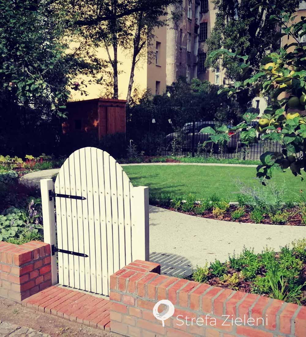 Biała furtka do ogrodu, ścieżki trawnik, murek z cegły