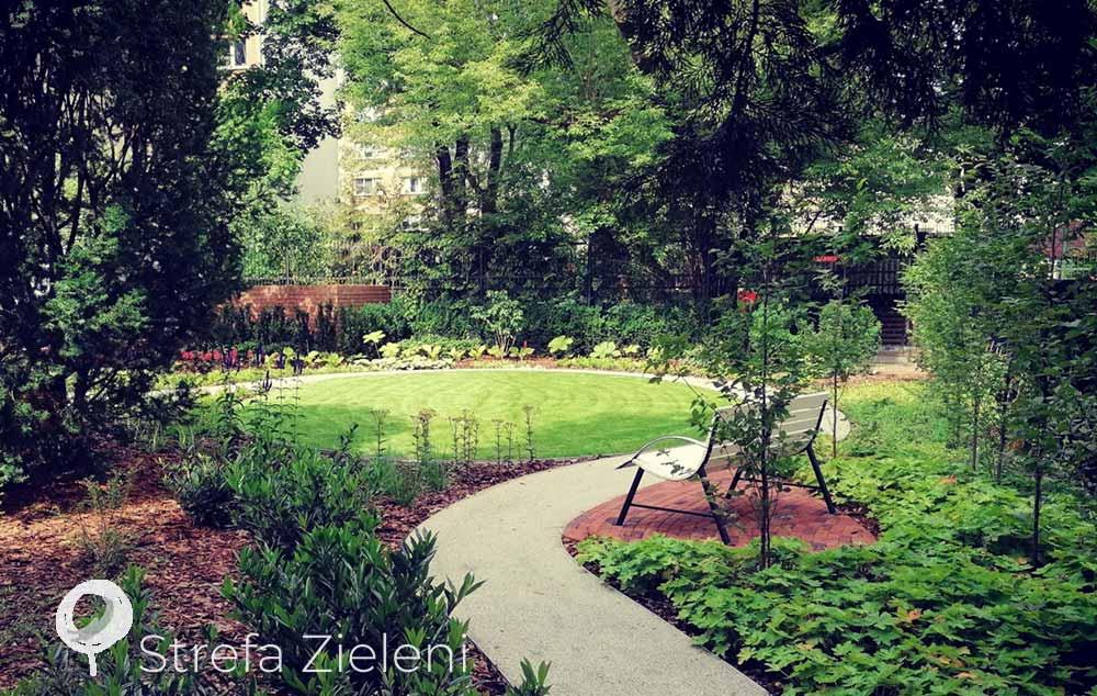 Miejsce wypoczynku w ogrodzie, biała ławka, nawierzchnia z kruszywa, nawierzchnia z cegły, owalny trawnik, bodziszek okrywowy
